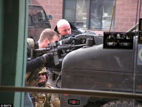 Yes, the EOTech is mounted backwards on the officer's carbine. That's not exactly confidence-inspiring.