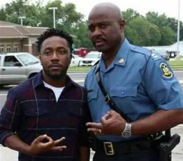 Missouri State Police Captain Ron Johnson making fraternity hand sign with Ferguson protestor